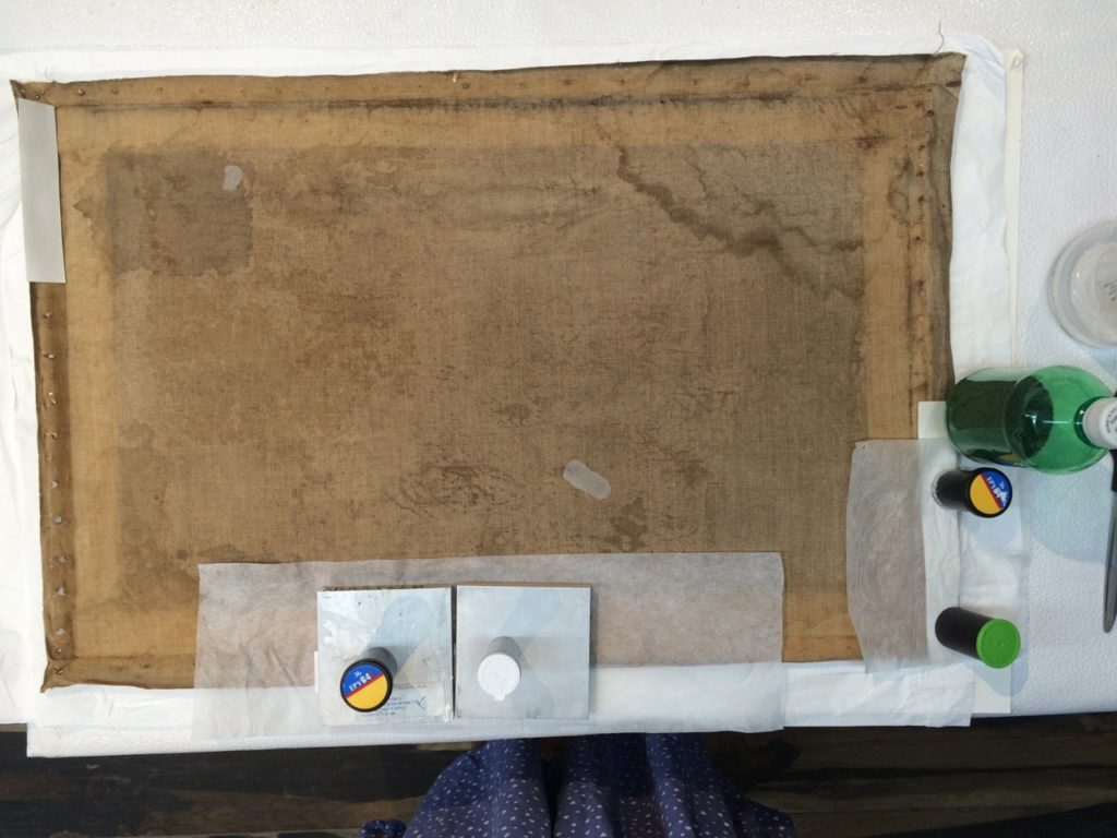 Flattening the canvas, in an effort to repair damage from the flat stretcher frame and years of neglect.